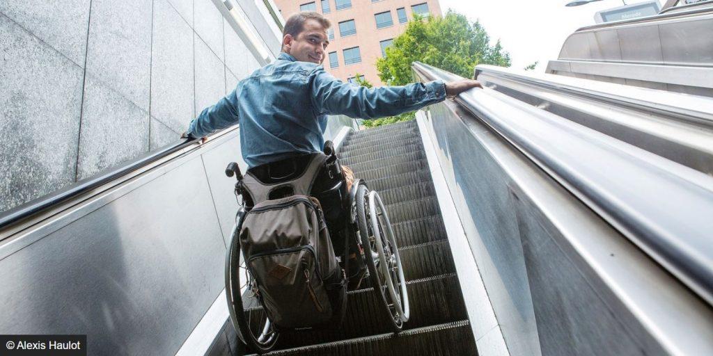 Nino Peeters formateur et conseiller en accessibilité sur un escalator en chaise roulante